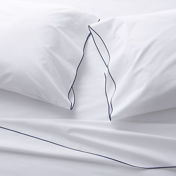 Clean, basic white bedding upgrades in soft, smooth cotton percale, beautifully contrasted with a graceful blue overlocking stitch on the flat sheet and pillowcase.