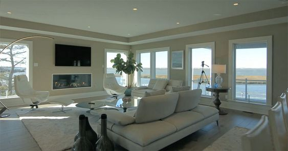 Luxury living room with modern fireplace and wraparound waterfront views.