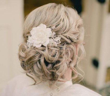 This bride's blonde hair is full of curls and pinned in a loose, romantic chignon. This hairdo is a classic look for weddings.