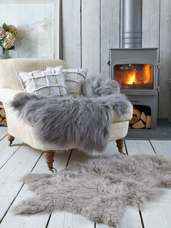 Cozy grey sheepskin rugs and throw in a Swedish living room with woodburning stove