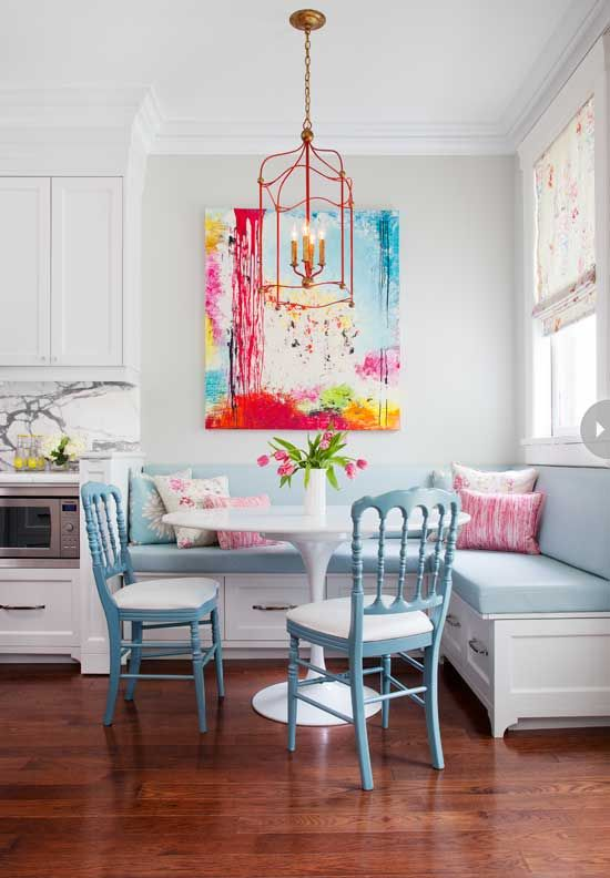Lovely colorful breakfast/ dining in the kitchen! Pastel blue banquette seating, Saarinen inspired table and blue painted chairs with a pop of brights in the art and light.: