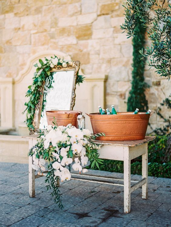 Distressed wooden table with drinks and covered in flowers: http://www.stylemepretty.com/2016/09/06/neutrals-color-palette-malibu-wedding/ Photography: Sally Pinera - http://sallypinera.com/