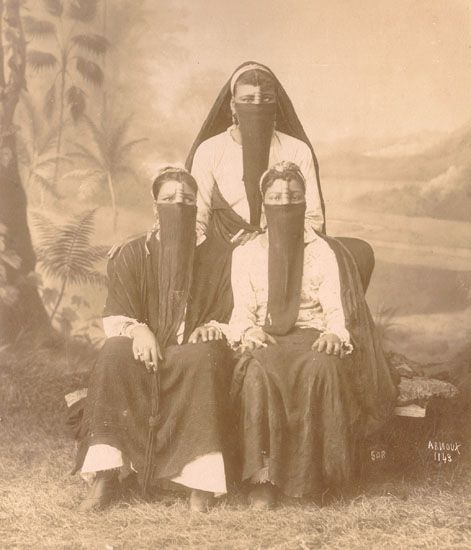 Hippolyte Arnoux - Three Veiled Arab Women, 1880s.  Each woman holds what appears to be a rolled cigarette.: