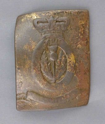 This is a brass cross belt plate of the 1st (Royal Scots) Regiment. It is rectangular with an oval scotch thistle in the centre with lettering (illegible) around it and a crown on top. There is also a banner at the bottom. The belt plate measures 5.5cm x7cm and 2 cm thick. Image courtesy of the Niagara Falls History Museum
