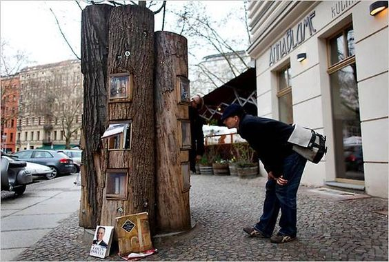 """""""Book Forest"""" is an outdoor, public bookcase in Berlin, designed to allow BookCrossing users to drop books they're done with so that others can take them in and read them. The """"forest"""" is made from hollowed out logs with protective clear doors."""