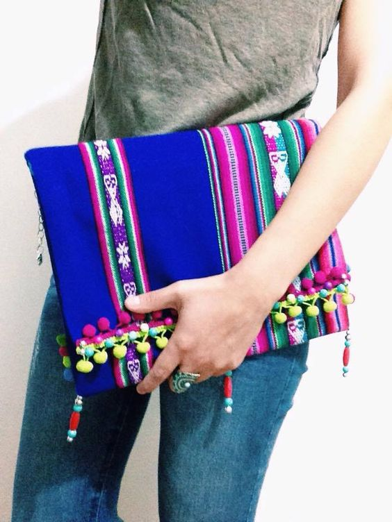 "Hand Bag /ethnic handle .Essential item for this season, with all the beauty of andean colours. Made of handicraft peruvian fiber (""Aguayo""), handmade embroidered with pompoms and attractive looking ornaments. Inside pocket covered in cloth similar to velvet. Inner zipper for more security."