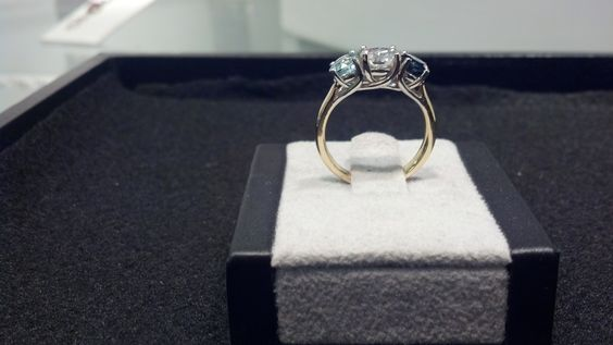 14K Yellow and White Gold Trellis ring with a center Diamond and an Aquamarine and Sapphire as accent stones.