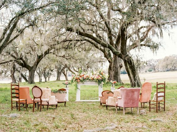 Vintage Outdoor Wedding Ceremony under Oak Trees with Mis-Matched Vintage Upholstered Chairs | Tampa Bay Vintage Wedding Rentals by Tufted Vintage Rentals
