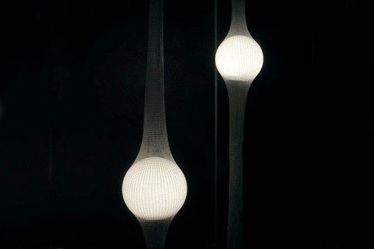 Ryosuke Fukusada's Net Lamps place efficient LED lamps as glowing orbs suspended within crocheted nets. Hanging Net Lamps combine elastic Poly-net knitted into a tight column, which, suspended from metal loops on the floor and ceiling, hold the lamp in mid-air as it softly illuminates the unusual surrounding fabric.