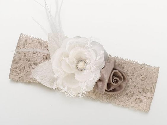 Vintage Lace Wide Bridal Garter features an elastic band made of intricate lace that is available in taupe or white. The front of the band is decorated with two fabric flowers. One flower is made of sculpted satin in the shape of a rose. The other flower is made of layered taupe fabric and lace with a faux pearl and rhinestone center. There also white feather accents extending out from behind the large flower.