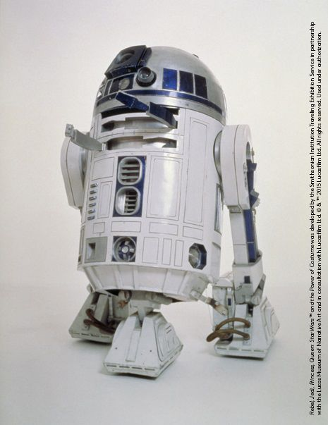 Actor Kenny Baker was able to look out of the eye in R2-D2's distinctive dome, and rotate the loveable Droid's head on a ball-bearing track. Industrial hosing was used to conceal a portion of the actor's legs that were visible between the body and feet. Design by: Ralph McQuarrie #StarWarsCostumes #behindtheseams