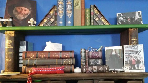 Use antique books without destroying them.  Put plain flat bookend inside the book and place a shelf over it.  Wrap the shelf in any wrapping paper that fits with your decor.  More room for photos and essentials.