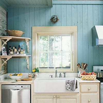 Blue Cottage Sink | A pretty blue backdrop and window frame the farmhouse sink. Meanwhile, salvaged corbels support the corner shelves nearby and add character to the area. | SouthernLiving.com