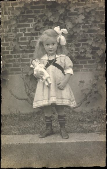 Little girl with doll in sailor dress: