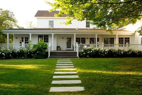 Old white farmhouse with wraparound porch