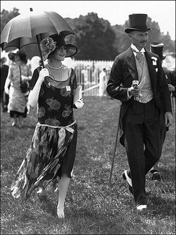 Fashionable man and lady, complete with top hat and parasol, at the races.1925