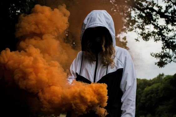 #human  #person  #smoke #woman #in #black  woman in black and white zip-up hoodie near orange smokes under a tree Exploration always turns into great photo opportunities. Don't be scared of doing things. Immerse yourself in what you love and enjoy.