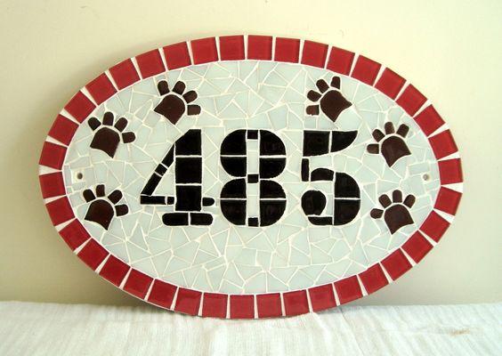 Numero residencial em mosaico, tamanho oval médio (38x25). Cliente pode escolher cor da borda e do número. O mosaico é realizado em cima de um piso e deverá ser fixado na parede com argamassa. Ou poderá ser feito 2 furos para parafusar na parede a pedido do cliente.