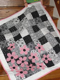Love the pink flower appliques on a simple quilt pattern.