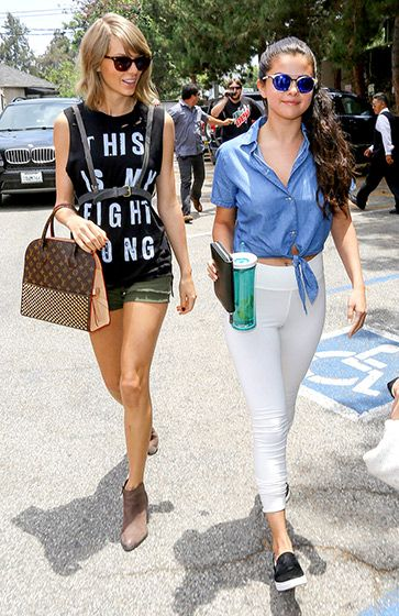 Taylor Swift wore a black t-shirt, green shorts, brown ankle boots, and a Louis Vuitton purse while strolling with pal Selena Gomez, who wore a blue button-up, white pants, and sneakers.