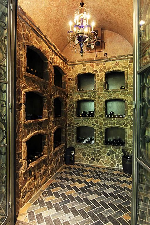 Most unusual refrigerated wine room with brick arches and openings for wine bottles, barrel vaulted ceiling, glazed tile flooring, and hand made wrought iron door.