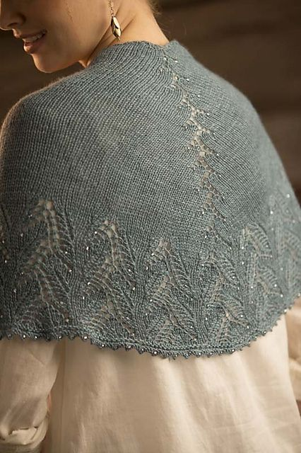 In this triangular shawl design, the spine has been reworked and hidden in plain sight. Asymmetrical, it is a piece of the border pattern taken out of context and beaded to emphasize its lovely draping stitches down into the leafy edging.