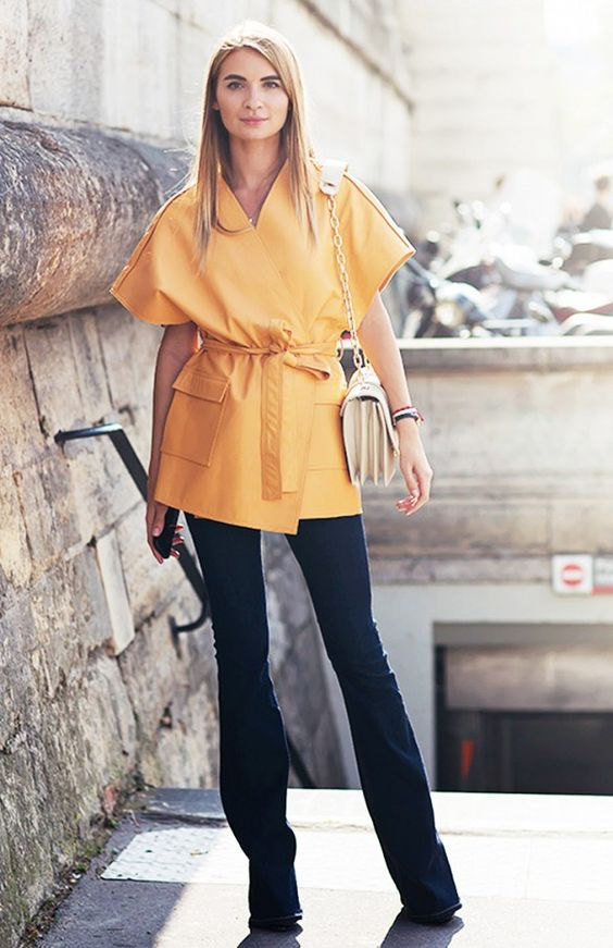 An orange wrap tunic is paired with flared trousers and a chain shoulder bag