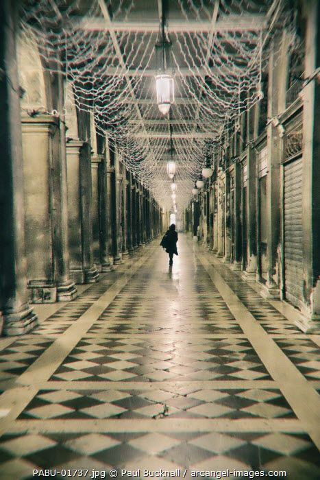 www.arcangel.com - a-shadowy-female-figure-walks-past-the-cafe