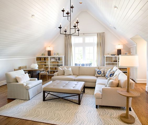 source: Tracy Hardenburg Designs Monochromatic family room with vaulted ceiling accented with beadboard trim punctuated with pot lights and iron chandelier over cream sectional sofa paired with cream tufted ottoman, rope floor lamp over white and gray zebra rug, West Elm Safari Wool Rug layered over oak wood floors. Attic family room features white bookcases flanking windows covered in cream silk curtains.