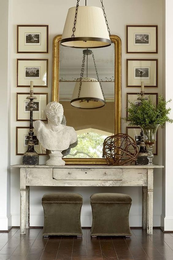 Beautiful Classically Refined Rooms. Entry decor with console table, bust, framed prints, and mirror.