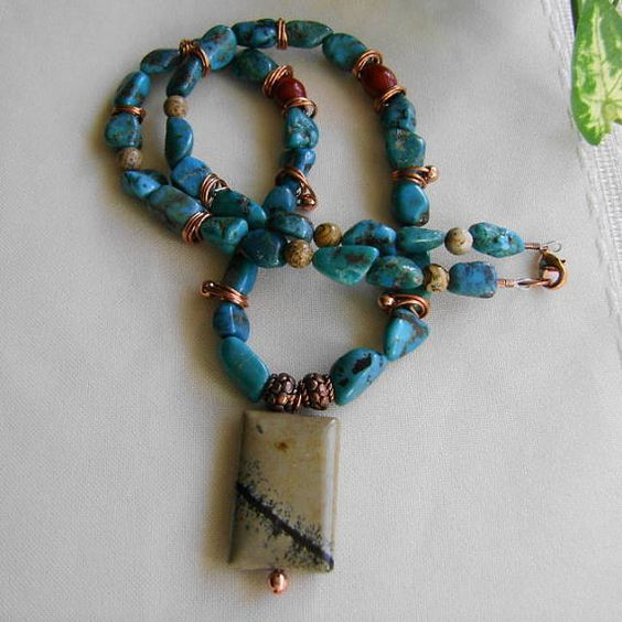 Polished nuggets of Arizona turquoise are featured with hand coiled copper and a painted jasper pendant. Textured copper beads, barrels of red