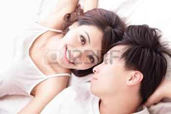 junge sch�ne Paar in einem Bett liegt, suchen gl�cklich l�cheln einander, Ansicht von oben, Asiaten photo