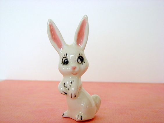 Cute little white porcelain rabbit with cartoon eyes. Stands upright, extra long ears, white with pink and black handpainted accents.  Measures 3