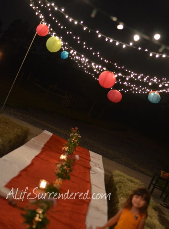 String lights and hang lanterns for summer outdoor party at night. Pool parties, snacks by the ...