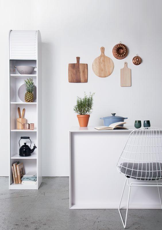 Witte keuken met houten accessoires en diebladen aan de muur. aan ...