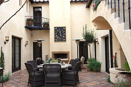 Kitchen courtyard is built out to include a tile patio and outdoor fireplace after remodeling - Spanish