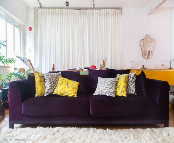 Sala de estar integrada com sofá roxo e almofadas amarelas estampadas.: