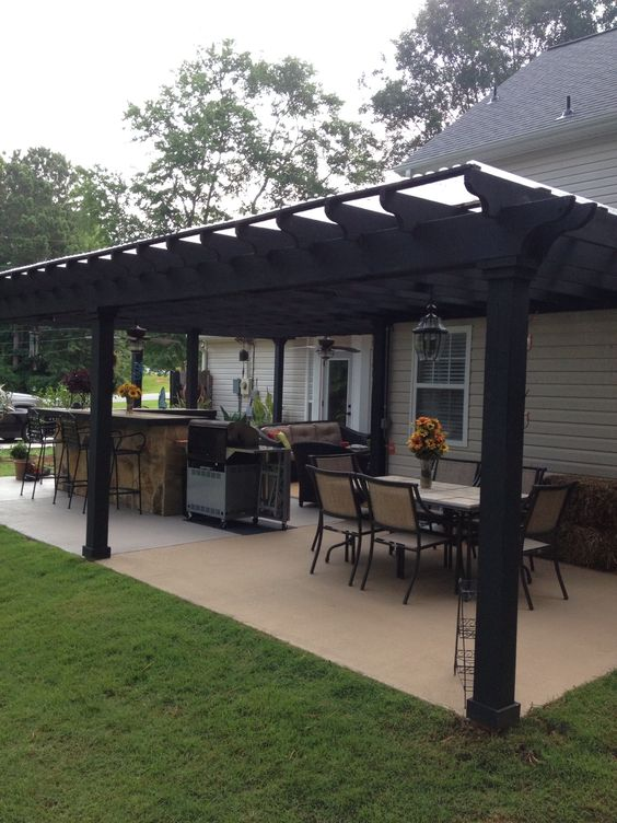 I like this open layout. Like the pergola over the table, grill, and bar. Don't like the plastic on top and wouldn't do ceiling fans or lanterns.  White Christmas lights would be prettier
