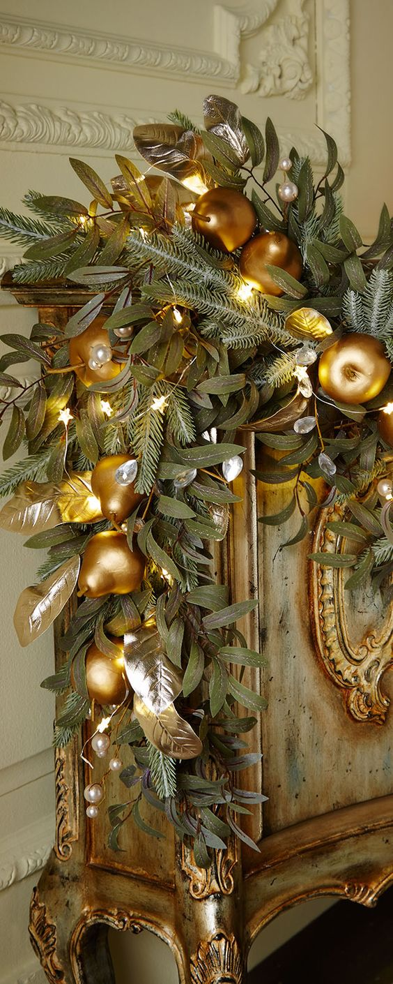 painted green and gold gilded cabinet with greens swag and gold ornaments