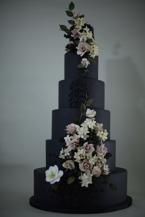 Designed by Victoria Made, this dramatic wedding cake features jet-black fondant accented with lifelike flowers, belladonna berries, and beading.