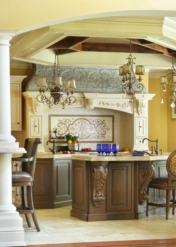 Scrolling chandeliers draw the eye upward to the kitchen's extraordinary ceiling. The hexagonal tray ceiling features recessed lighting and dark-stained beams.