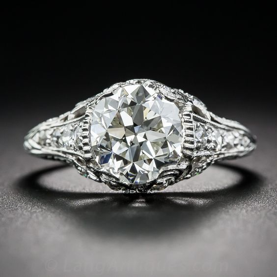 An absolutely gorgeous European-cut diamond, weighing 2.09 carats, beams brilliantly from within an original platinum and diamond mounting dating from the early-twentieth century. The splendid ring, which you can tell from the all around hand engraving has never been resized, is adorned with a characteristically Edwardian diamond-set bow motif doing double-duty as the decorative side gallery and the prongs. The shoulders are adorned with tapering rows of tiny sparklers leading to the…