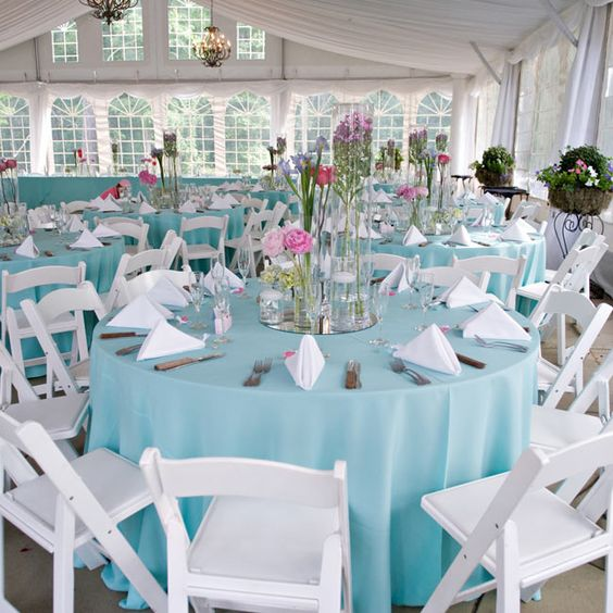 Chandeliers, sky blue linens and pink centerpieces dressed up the airy tent. Mossy arrangements on wrought iron pedestals lined the peripher...