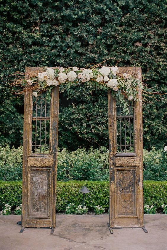 Small wooden doors with center florals for a ceremony backdrop: