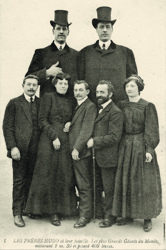 Brothers Baptiste (7'6'', 1887-1914) and Antoine Hugo (7'5'', 1876-1916) both had gigantism from pituitary tumors. They are shown here with their family.: