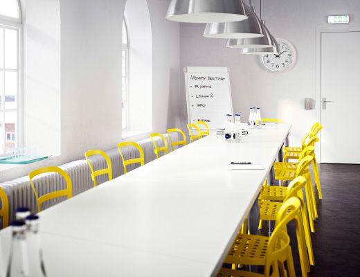 Mesa de reuniones grande, blanca, con sillas amarillas
