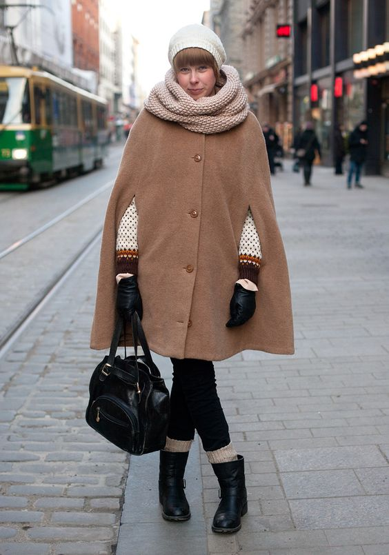 """Anna, 23    """"The cape is from Vintage Ansa and it's also called Anna. The beanie is a gift from a friend, the scarf is self-made, the pullover and the bag are second hand.    I like nude, beige and other down-to-earth colours. I like loose, comfortable and droopy clothes like big pullovers.""""  24 February 2011"""