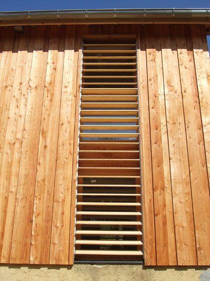 Détail du bardage vertical en mélèze et des persiennes orientables