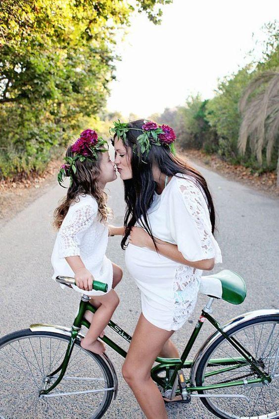 Sesión de fotos mamá besando a su hija mientras están en una bicicleta