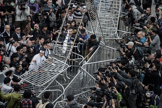 Umbrella Revolution Hong Kong, Security staff members remove a barricade outside the Citic tower near a protest site in the Admiralty district of Hong Kong on November 18, 2014. Security staff members assisted by Hong Kong bailiffs took action at pro-democracy barricades outside the building located near the main protest sites in the city, as pressure grows on demonstrators to leave. AFP PHOTO / Philippe Lopez (Photo credit should read PHILIPPE LOPEZ/AFP/Getty Images)